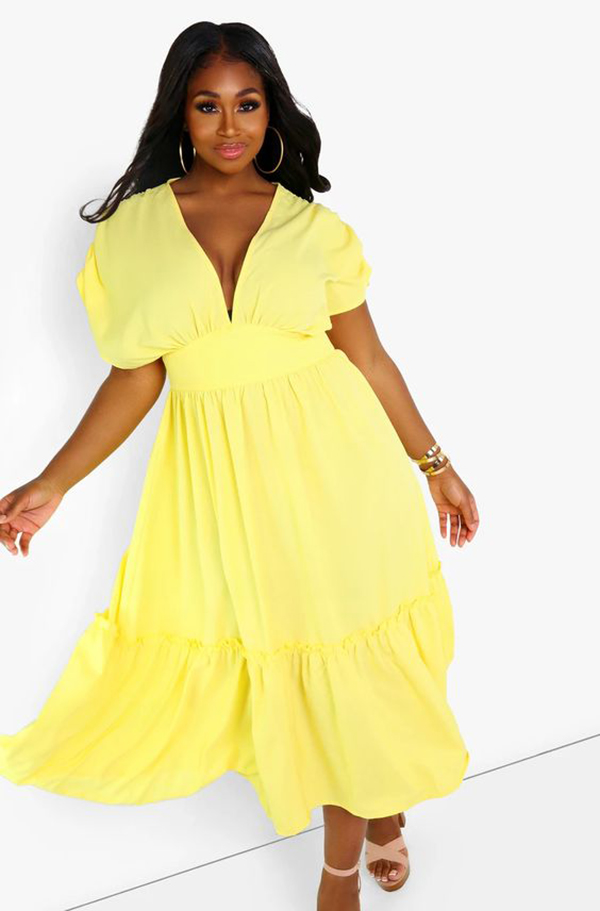 A plus-size model wearing a yellow dress.