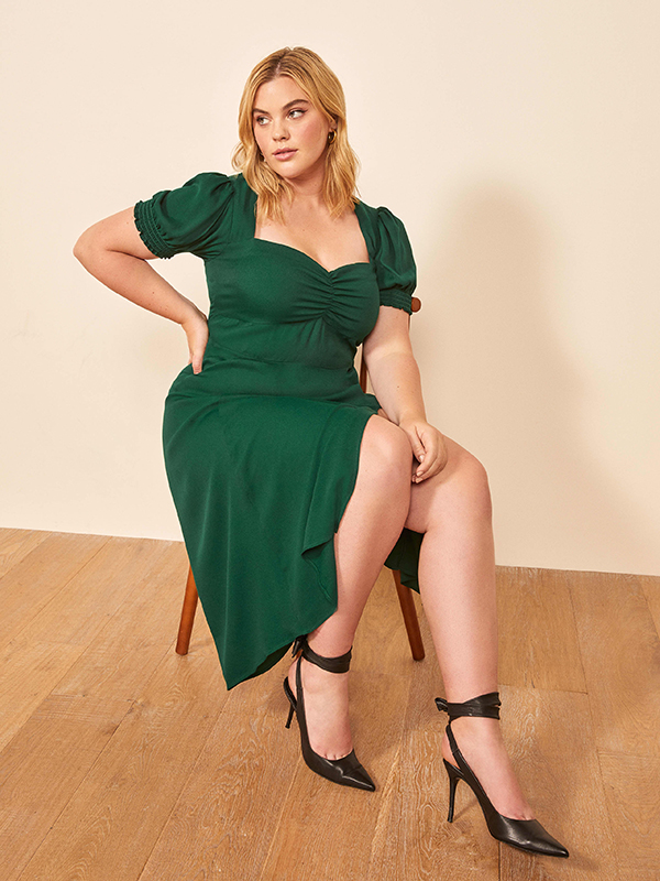 A plus-size model wearing a green dress.