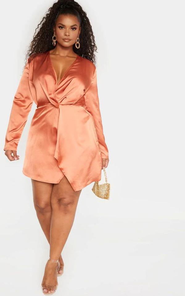 A plus-size model wearing a coral dress.