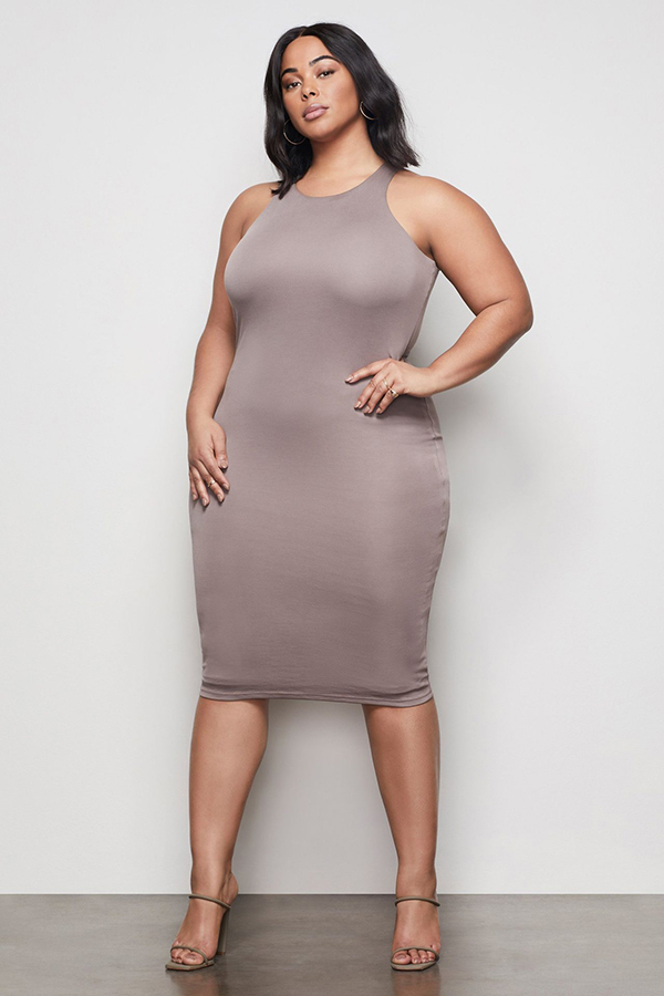 A plus-size model wearing a taupe form-fitting dress.