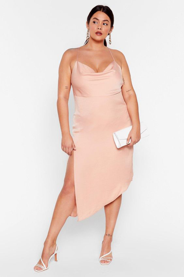 A plus-size model wearing a pink satin dress.
