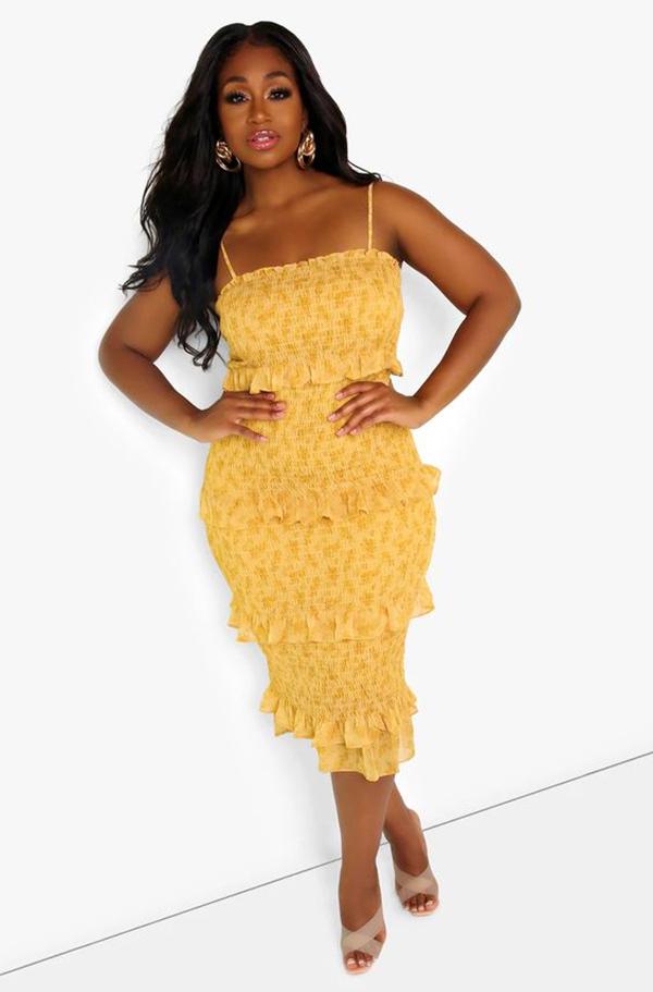 A plus-size model wearing a yellow shirred dress.