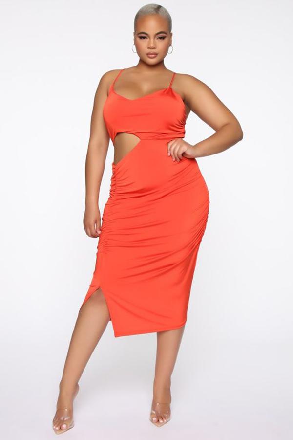 A plus-size model wearing a red-orange cutout dress.