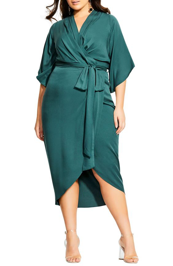 A plus-size model wearing a teal wrap dress.