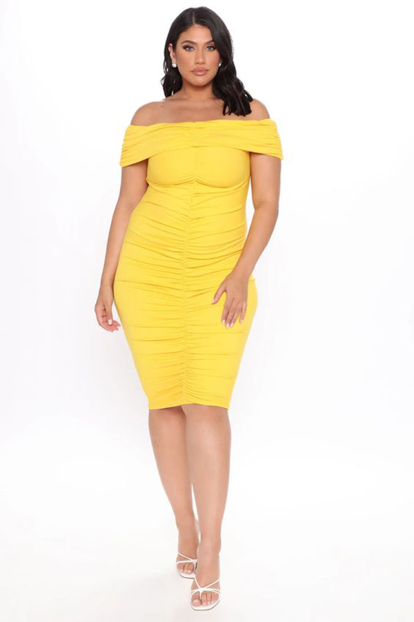 A plus-size model wearing a yellow off-the-shoulder dress.