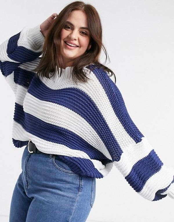 A model wearing a plus-size oversized sweater in blue and white stripe.