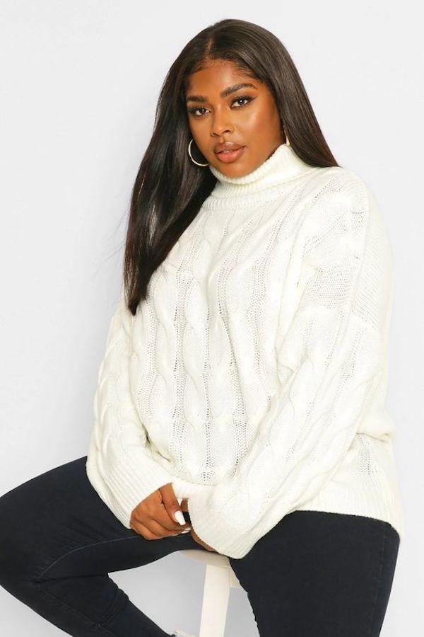 A model wearing a plus-size oversized sweater in cream.