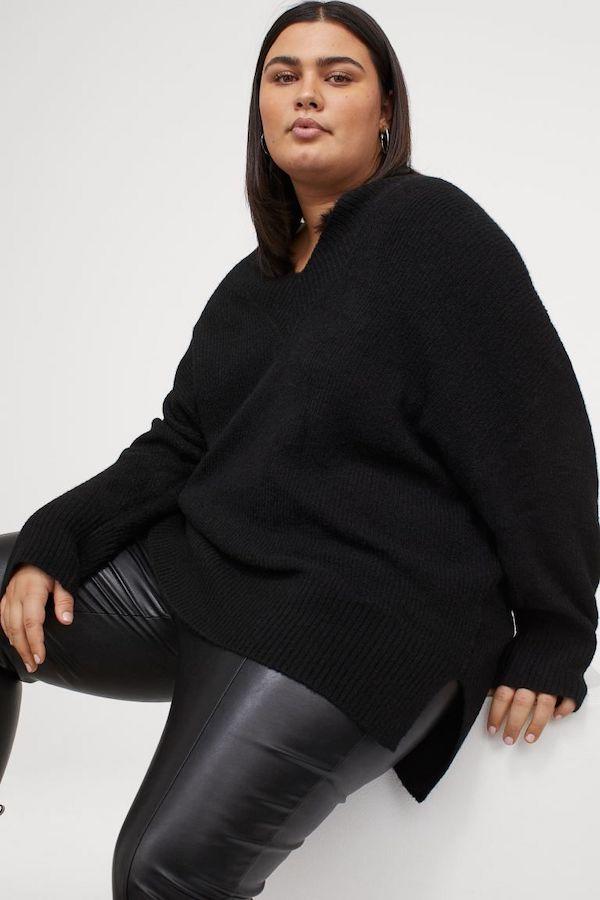 A model wearing a plus-size oversized sweater in black.