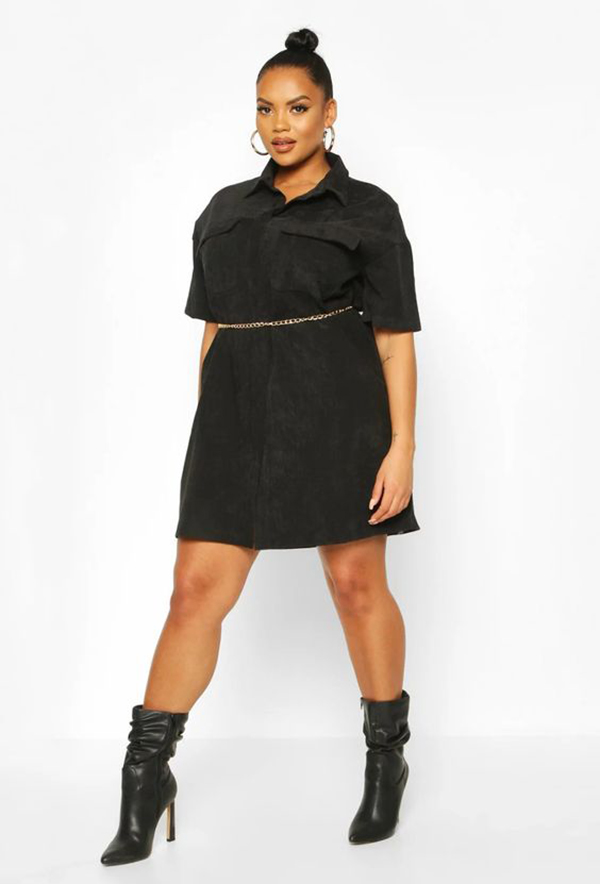 A plus-size model wearing a black corduroy dress.