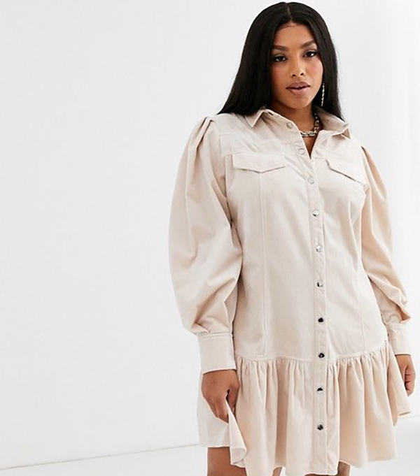 A plus-size model wearing a white corduroy dress.