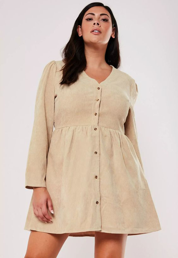 A plus-size model wearing a corduroy dress.