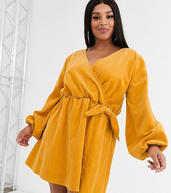 A plus-size model wearing a yellow corduroy dress.