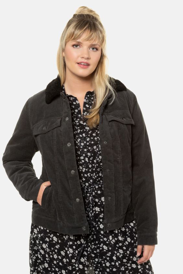 A plus-size model wearing a black corduroy shacket.