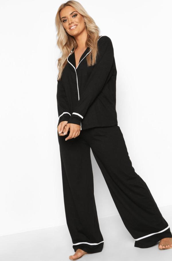 A plus-size model wearing a black pajama set.