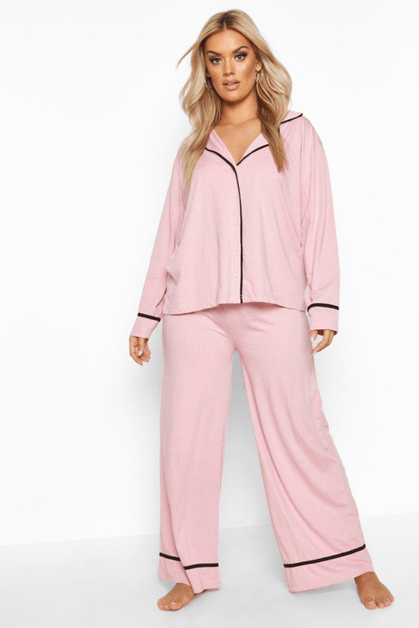 A plus-size model wearing a pink pajama set.