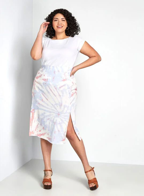 A model wearing a purple and pink tie-dye plus-size skirt.
