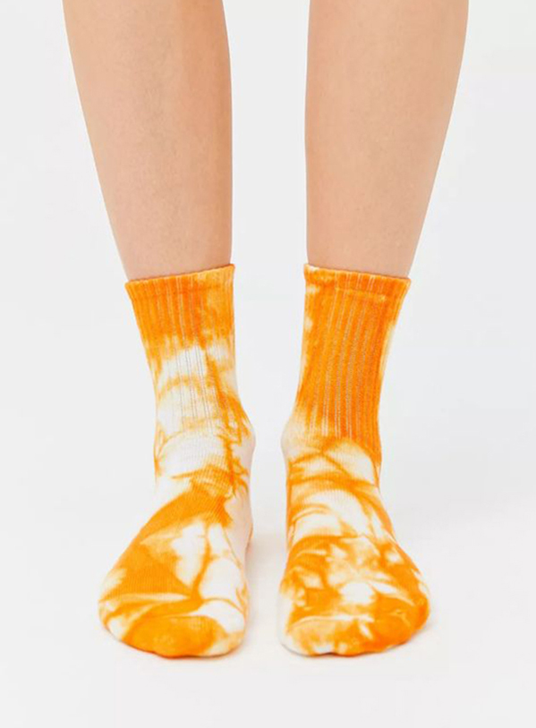 A pair of legs wearing orange tie-dye socks.