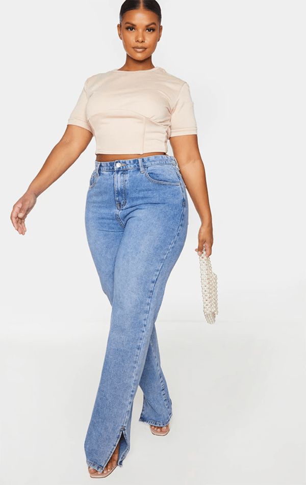 A plus-size model wearing a fitted off-white crop top.
