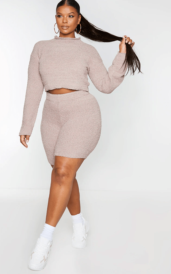 A plus-size model wearing a taupe turtleneck crop top.