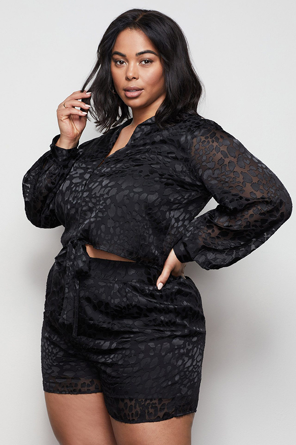 A plus-size model wearing a black satin crop top.