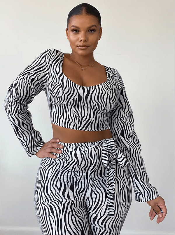 A plus-size model wearing a zebra print bustier crop top.