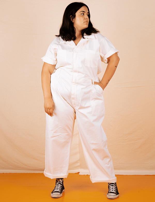 A plus-size model wearing a white utility jumpsuit.