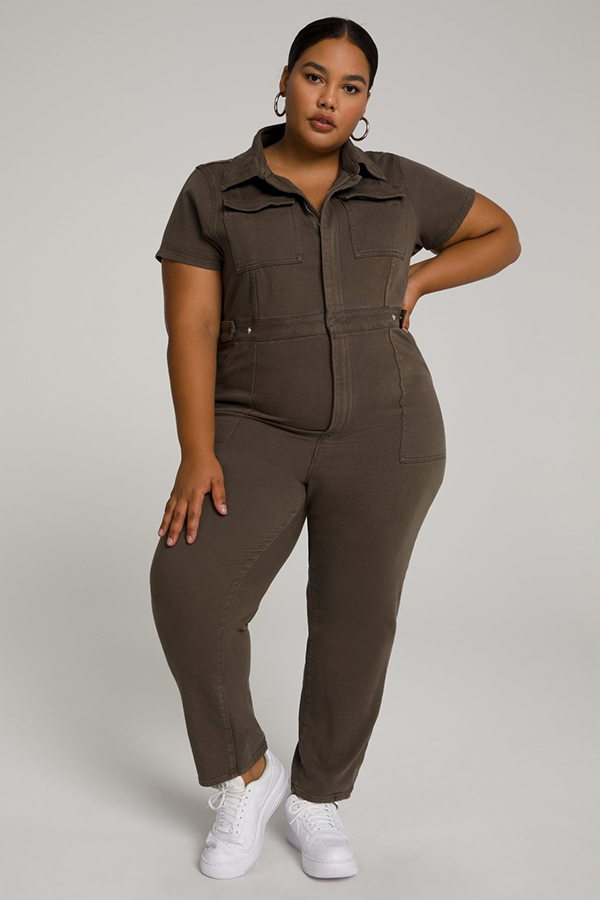 A plus-size model wearing a brown utility jumpsuit.