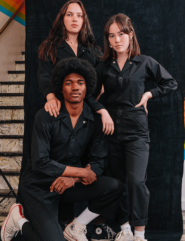 A group of models wearing black utility jumpsuits.