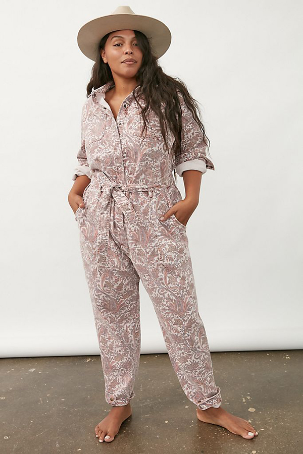 A plus-size model wearing a pink paisley utility jumpsuit.