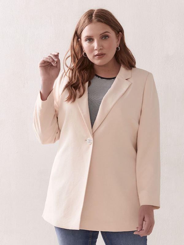 A woman wearing a light pink blazer.