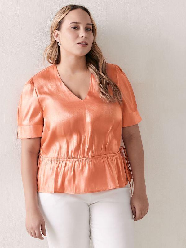 A woman wearing a coral peplum blouse.