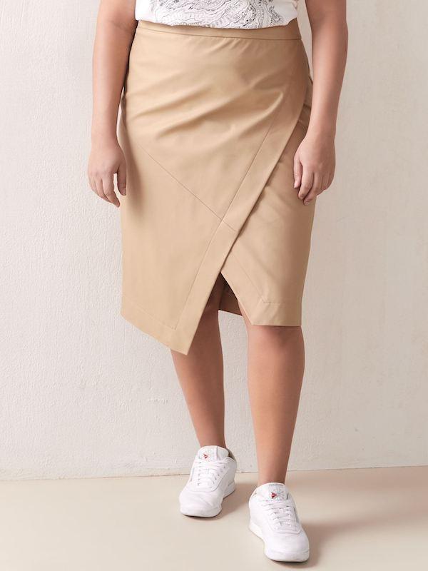 A woman wearing a tan faux wrap skirt.