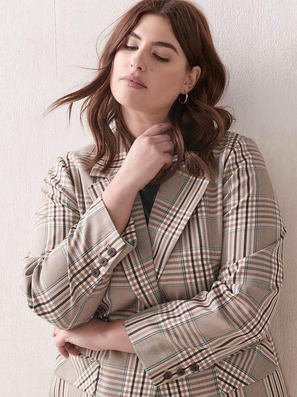 A woman wearing a plaid blazer.