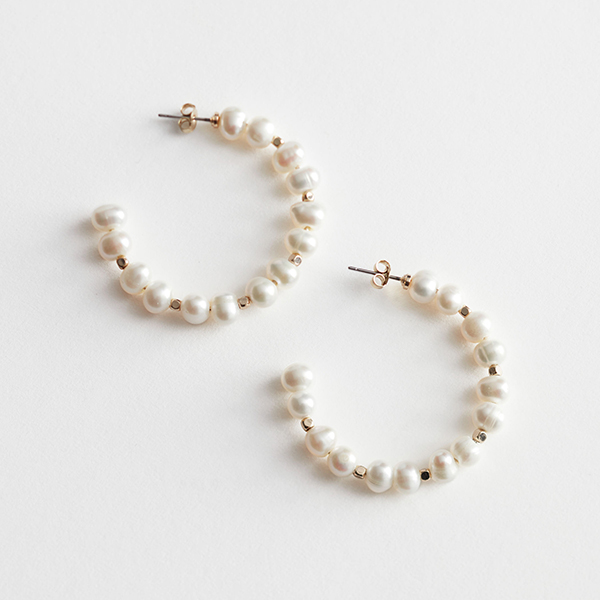 A pair of hoop earrings covered in pearls.