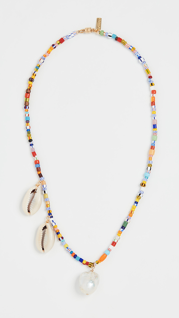 A rainbow beaded necklace with shells and pearls hanging off it.