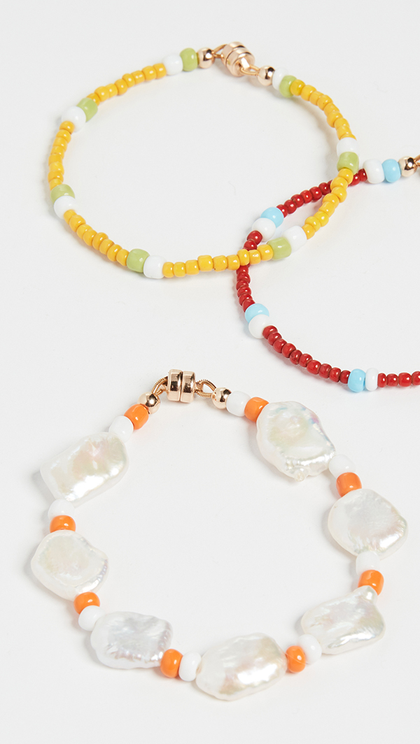 Several beaded bracelets, one of which is crafted from large pearls and orange seed beads.