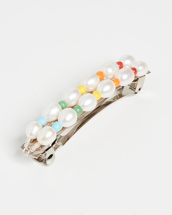 A barrette covered in pearls and rainbow beads.