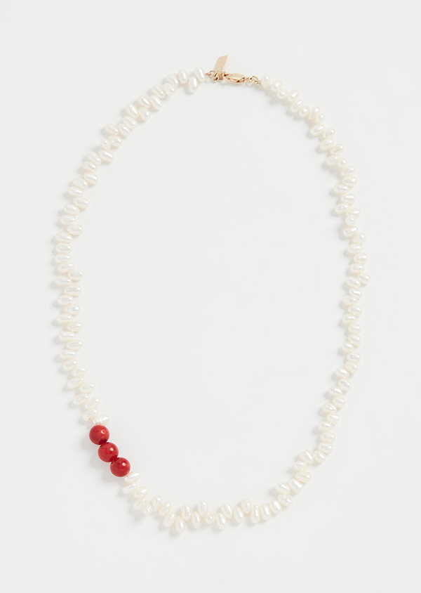 A pearl necklace with three red beads on it.
