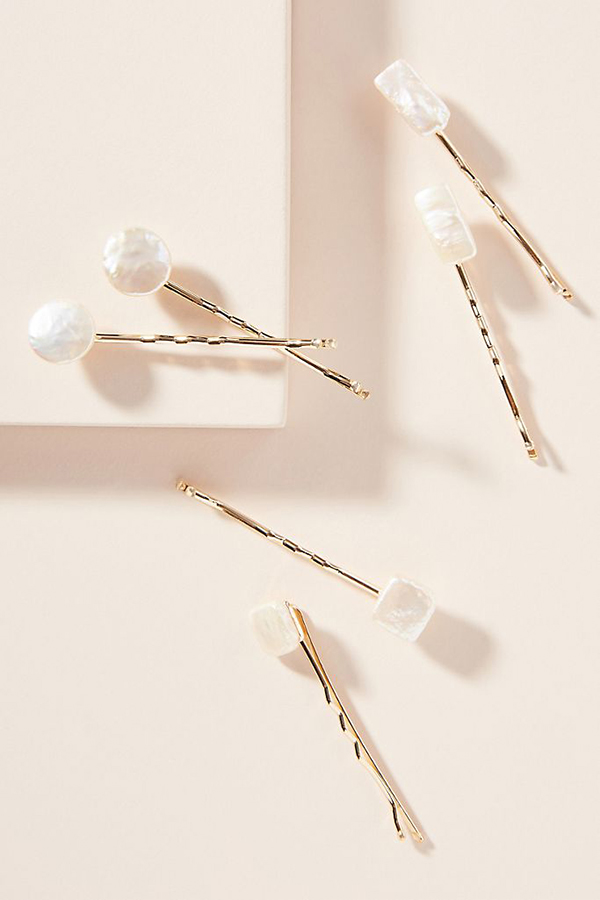 A set of bobby pins that have small pearls on them.