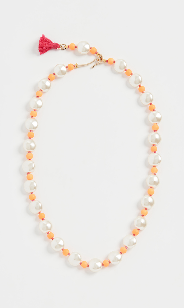 A pearl necklace punctuated by orange beads.