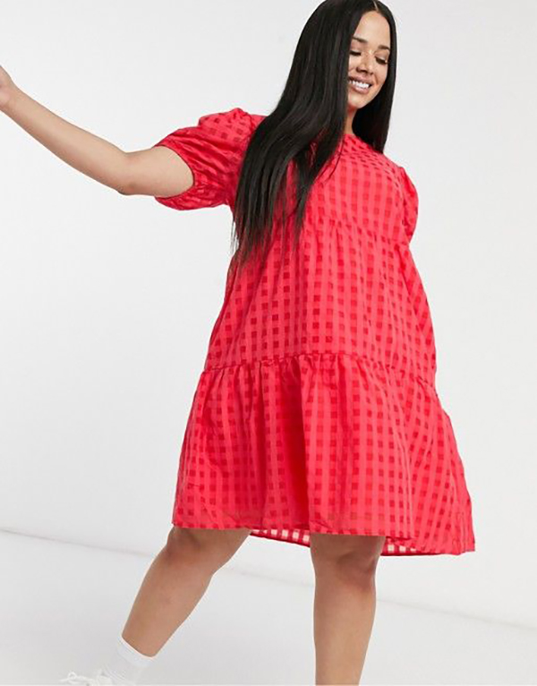 A plus-size model wearing a red babydoll dress.