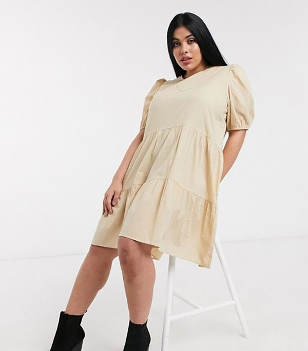 A plus-size model wearing a babydoll dress.