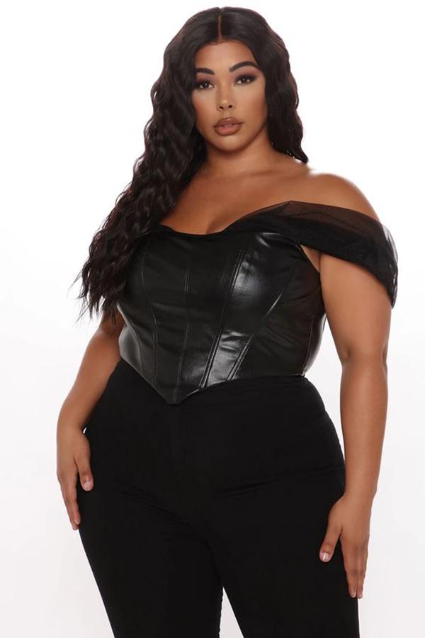 A plus-size model wearing a black bustier top.