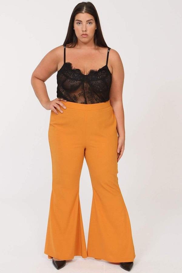 A woman wearing a black top and mustard flare pants.