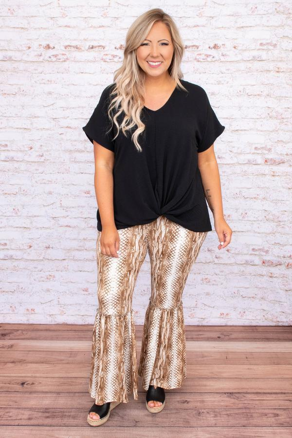 A woman wearing a black top and snake print flare pants.