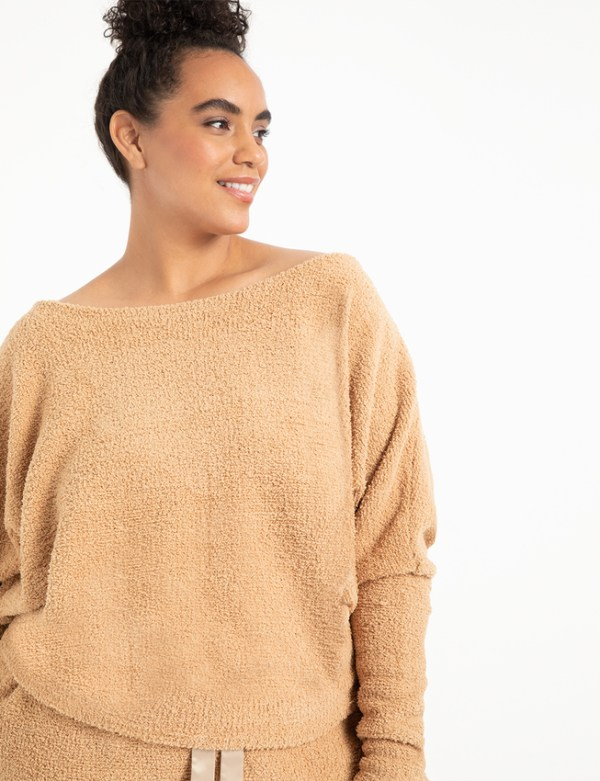 A woman wearing a light brown fuzzy sweatshirt.