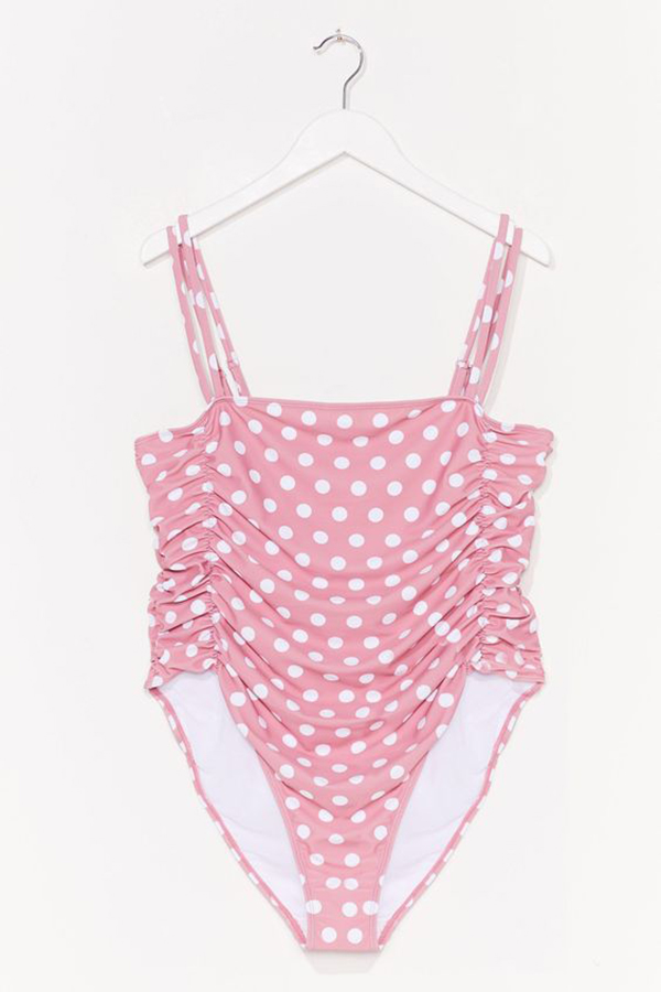 A plus-size, pink and white polka dot, one-piece swimsuit hanging on a hanger.