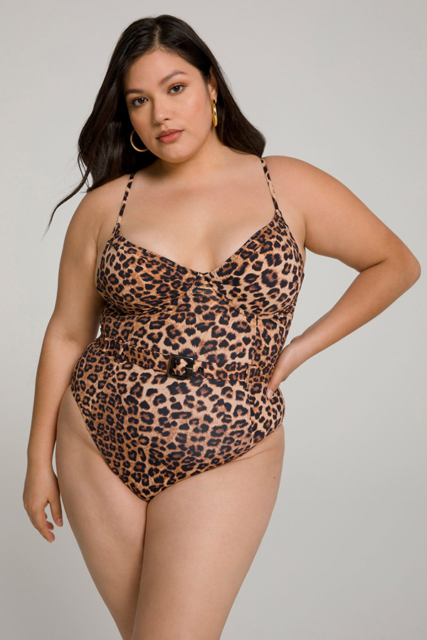 A plus-size model wearing a cheetah print, belted one-piece swimsuit.
