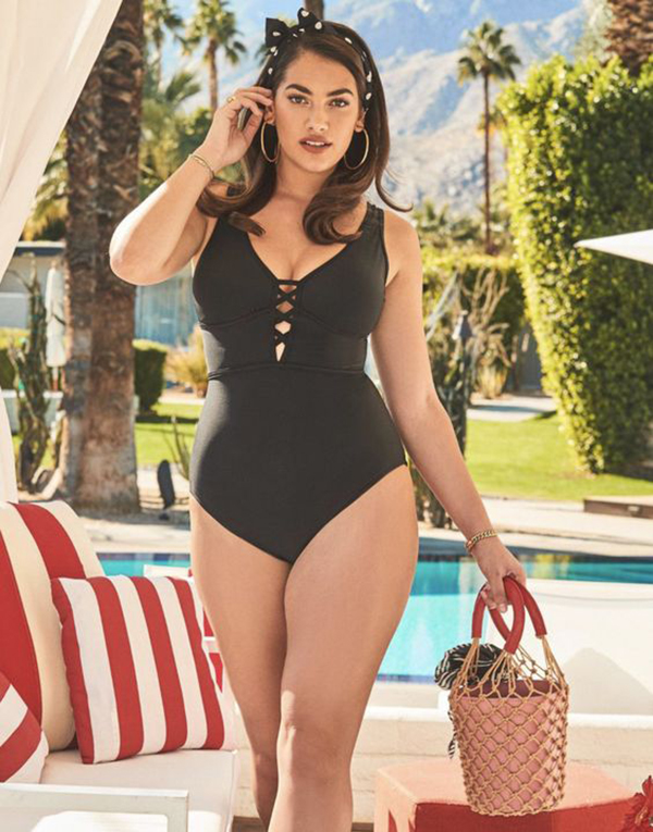 A plus-size model wearing a black one-piece swimsuit.