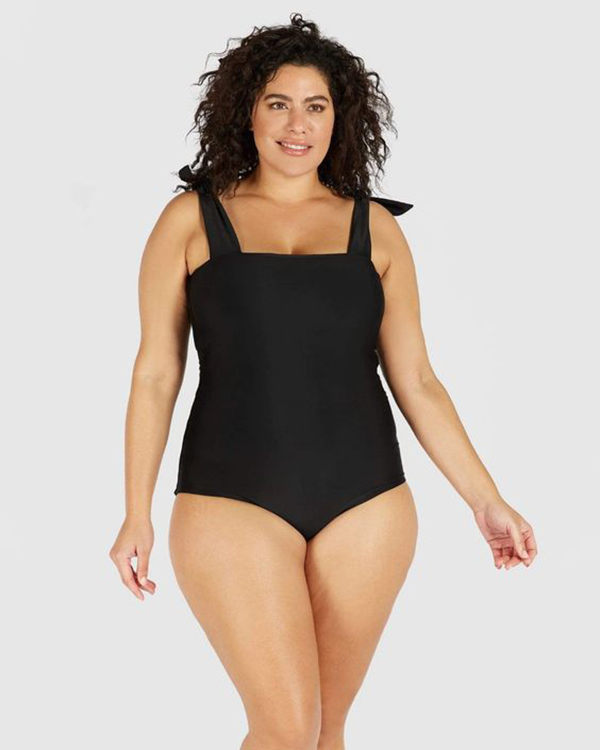 A plus-size model wearing a black, tie-strap one-piece swimsuit.